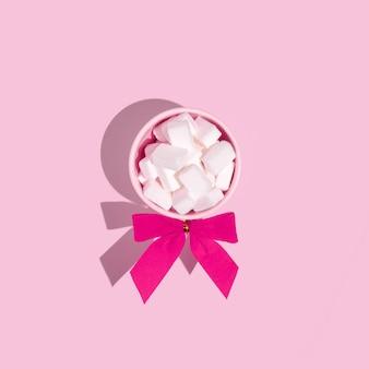 Kleine roze kopjes gevuld met suikerklontjes op een zachtroze ondergrond. platliggende compositie.