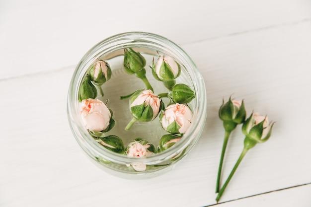 Kleine roze rozen met toppen in glazen pot op witte houten planken achtergrond, bovenaanzicht