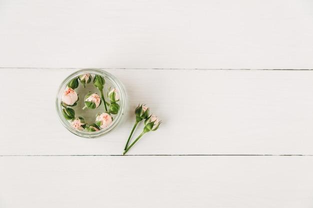Kleine roze rozen met toppen. minimalistische compositie, eenvoudige witte achtergrond. kopieer de ruimte. platte lay