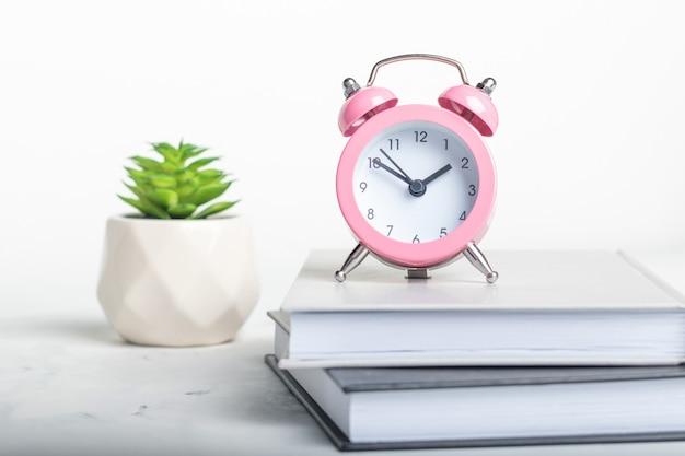 Kleine roze wekker staat op een stapel boeken op een witte marmeren achtergrond