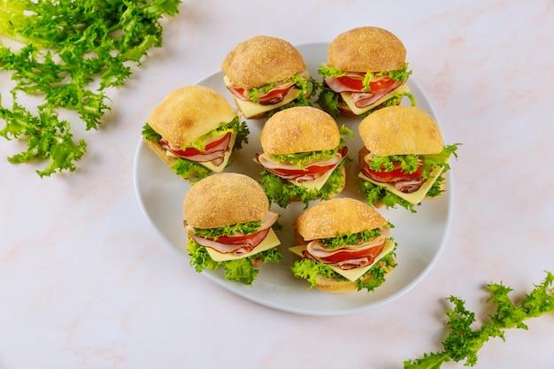 Kleine sandwiches met ham en kaas op plaat op houten tafel