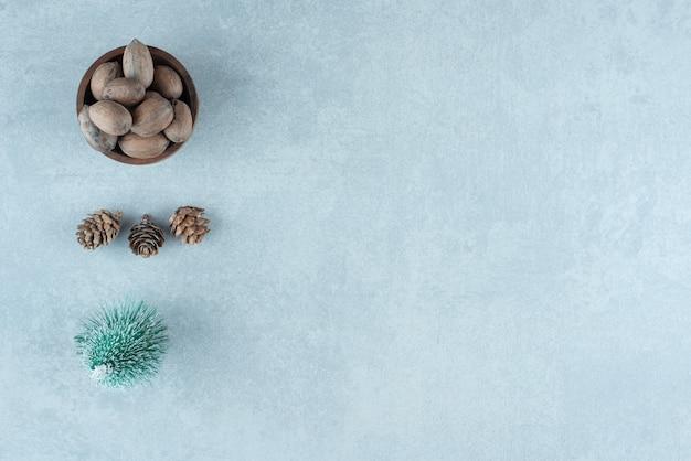 Kleine schaal met amandelen, dennenappels en een boombeeldje op marmer.
