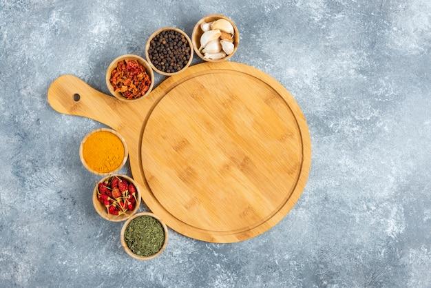 Kleine schaaltjes met kruiden rond een houten bord.
