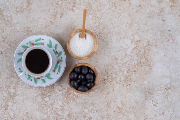 Kleine schaaltjes suiker en snoep naast een kopje koffie