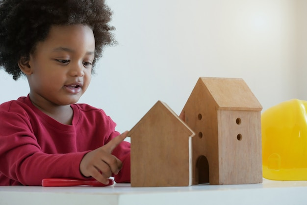 Kleine schattige afrikaanse jongen spelen met houten huis