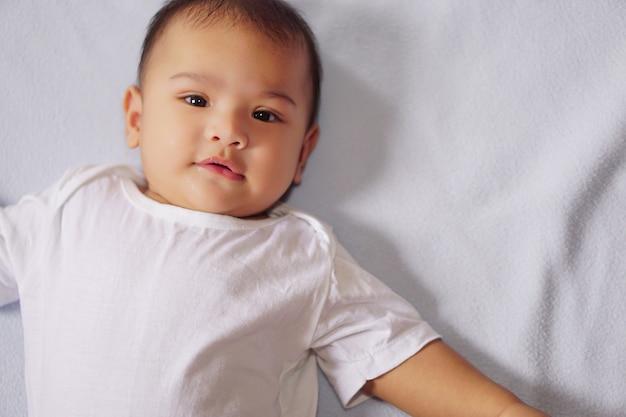 Kleine schattige baby die blauwe matras ligt en naar de camera kijkt het concept van empathisch schattig