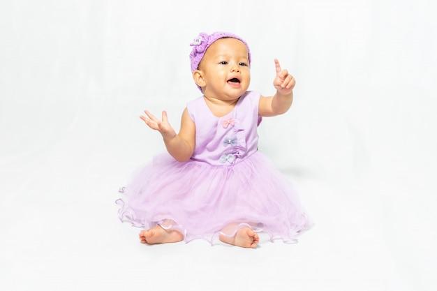 Kleine schattige baby, leeftijd 9-10 maand, aziatisch meisje draagt lichtpaarse jurk op witte achtergrond.