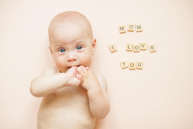 Kleine schattige baby ligt op een lichtroze achtergrond. ernaast staat een inscriptie uit houten blokken