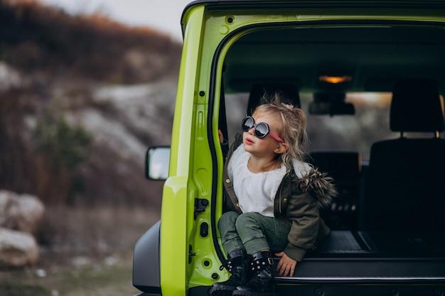 Kleine schattige baby meisje zit in de achterkant van de auto