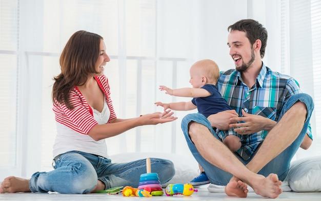 Kleine schattige baby van zes maanden oud met ouders