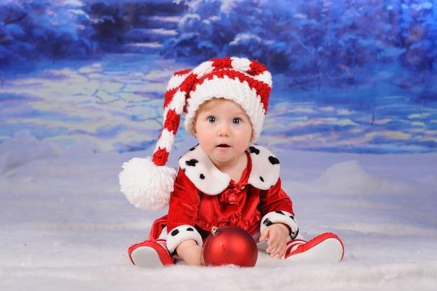 Kleine schattige baby zit in de sneeuw in een kerstmuts. Premium Foto