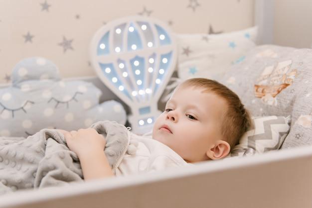 Kleine schattige babyjongen ligt in de kinderkamer in een houten bedhuis met nachtlampjes in de vorm van een ballon, baby valt in slaap in de wieg