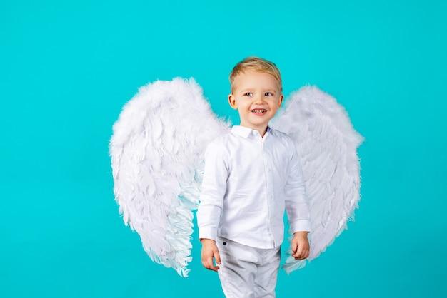 Kleine schattige babyjongen met blond lang met witte engelenvleugels.