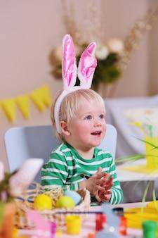 Kleine schattige babyjongen met wit haar met konijnenoren op zijn hoofd zitten aan een tafel voor een mand en decor van pasen.
