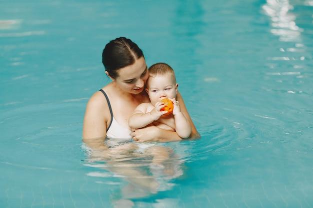 Kleine schattige babyjongen. moeder met zoon. familie spelen in een water