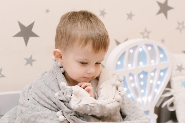 Kleine schattige babyjongen zitten in de kinderkamer in een houten bed huis met nachtverlichting in de vorm van een ballon