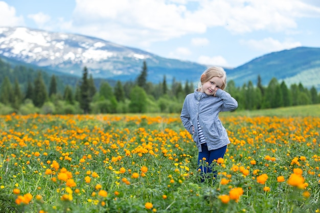 Kleine schattige babymeisje is mooi en gelukkig, glimlachend in de zomer in de wei tegen de bergen met sneeuw