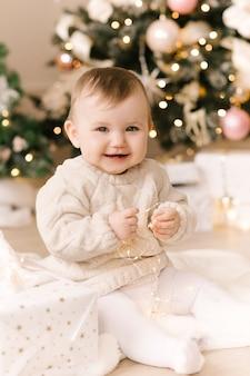Kleine schattige babymeisje onder de kerstboom. fijne feestdagen, gelukkig nieuwjaar. kersttijd