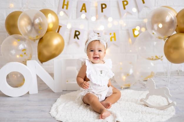 Kleine schattige babymeisje zit met de letters één en ballonnen, eerste jaar, verjaardag, vakantie