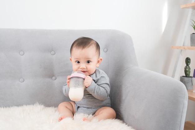 Kleine schattige babymeisje zittend in de kamer op de bank melk drinken uit de fles en glimlachen. gelukkig kind. familie mensen binnen interieur concepten. beste tijd uit de kindertijd!