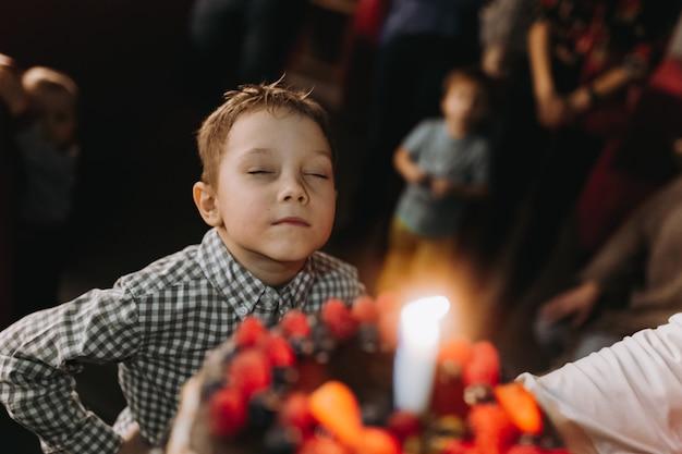 Kleine schattige blanke jongen die een wens doet voordat hij een kaars op een taart uitblaast op zijn 6e verjaardag