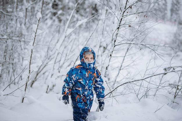 Kleine schattige blanke jongen die een winteroverall draagt met capuchon op en sneeuw op zijn gezicht in het winterbos