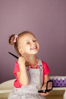 Kleine schattige blonde 3-4 jaar oud zit met een set cosmetica en doet make-up