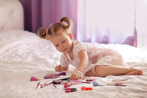 Kleine schattige blonde glimlacht drie - vier jaar met een kapsel naast een spiegel met een set cosmetica en borstels