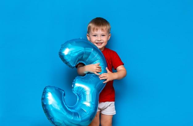 Kleine schattige blonde jongen houdt folie-gecoate bol ballon blauwe kleur. fijne verjaardag drie jaar oud