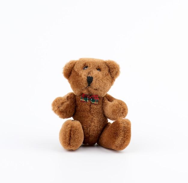 Kleine schattige bruine teddybeer met een strik in zijn nek