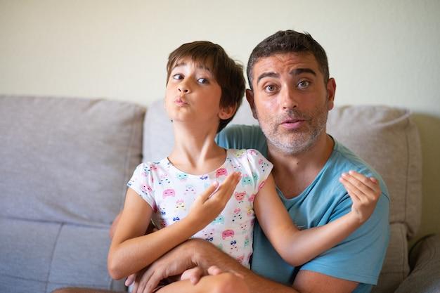Kleine schattige dochter doet make-up aan haar vader