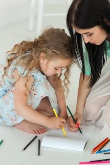 Kleine schattige dochter en haar moeder tekenen met kleurrijke potloden en samen plezier. mooi kind en moeder spelen binnenshuis. gelukkige familie tijd doorbrengen door te tekenen.