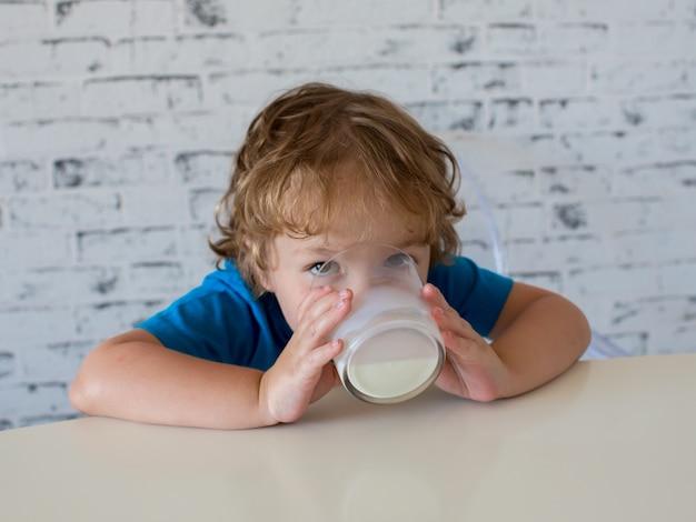 Kleine schattige jongen consumptiemelk uit een glas in de ochtend