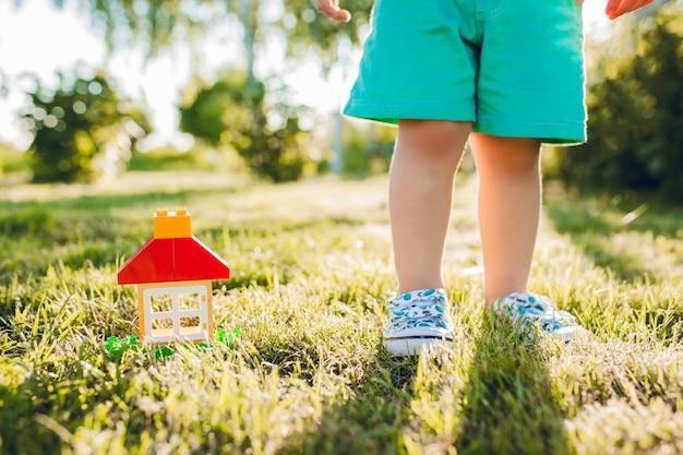 Kleine schattige jongen en zijn huis in de zomertuin.