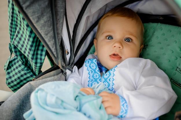 Kleine schattige jongen gekleed in het geborduurde shirt liggend in de kinderwagen