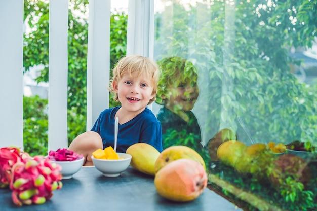 Kleine schattige jongen mango eten op het terras.
