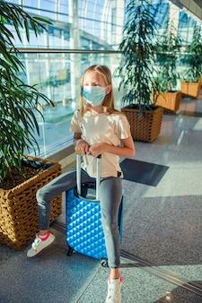 Kleine schattige jongen met chirurgische masker gezichtsbescherming op internationale luchthaven. bescherming tegen coronavirus en gripp