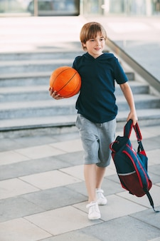 Kleine schattige jongen met een basketbalbal