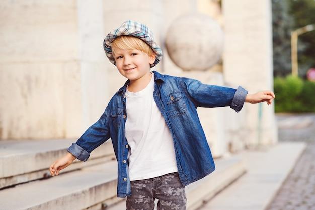Kleine schattige jongen met een hoed buiten lopen