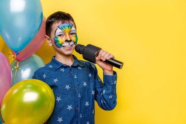 Kleine schattige jongen met schminken, met huidige kleurrijke ballonnen en microfoon terwijl hij geïsoleerd blijft op de gele muur.