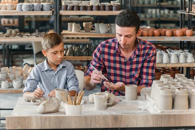 Kleine schattige jongen met zijn vader die keramische potten in het aardewerk maakt.