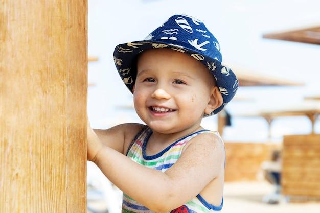 Kleine schattige jongen met zomerhoed speelt op het strand van het hotel.