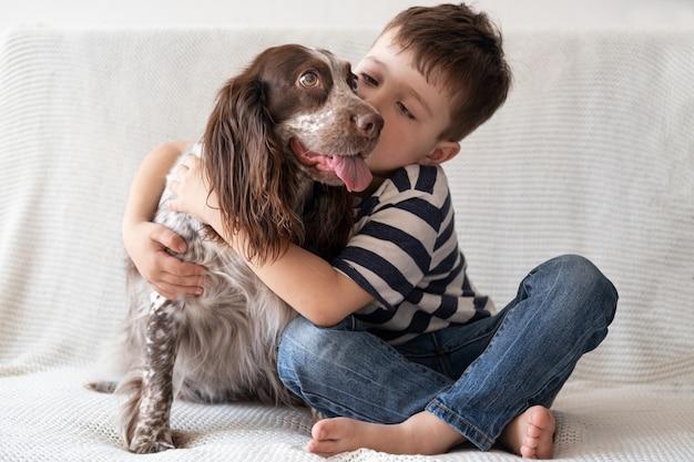 Kleine schattige jongen omhelzen kus russische spaniel hond chocolade merle verschillende kleuren ogen. zitten op de bank. huisdieren zorg concept.