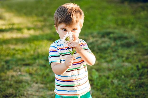 Kleine schattige jongen ruiken een bloem in de zomertuin en ziet er gelukkig uit.
