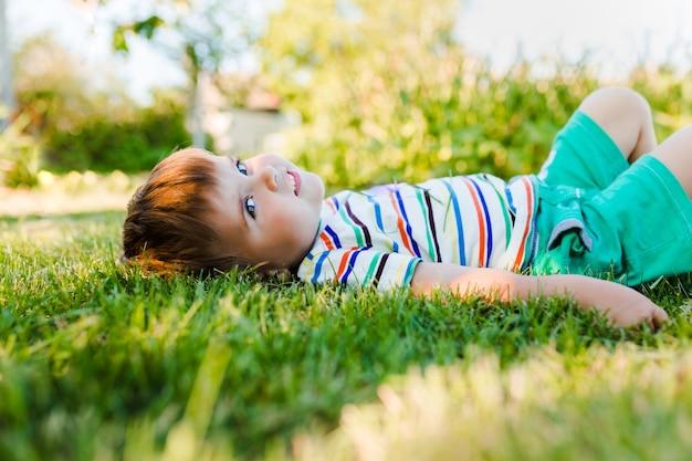 Kleine schattige jongen rustend op het groene gras in de tuin en ziet er gelukkig en ontspannen uit.