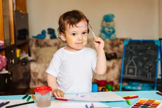 Kleine schattige jongen tekent met penselen en gekleurde verf op een vel papier