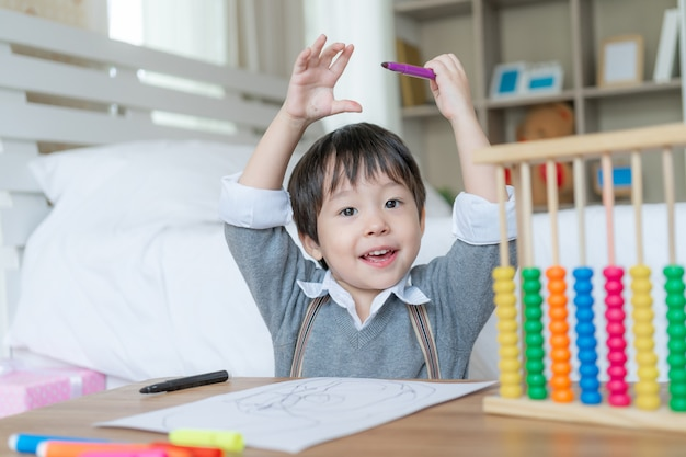 Kleine schattige jongen trots wanneer hij klaar is met tekenen met geluk, hief twee handen op zijn hoofd en glimlacht