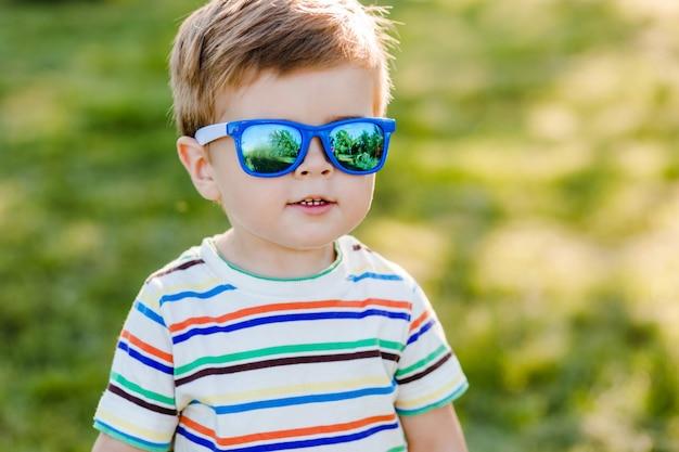 Kleine schattige jongen verblijft in de tuin in heldere zonnebril en glimlach.