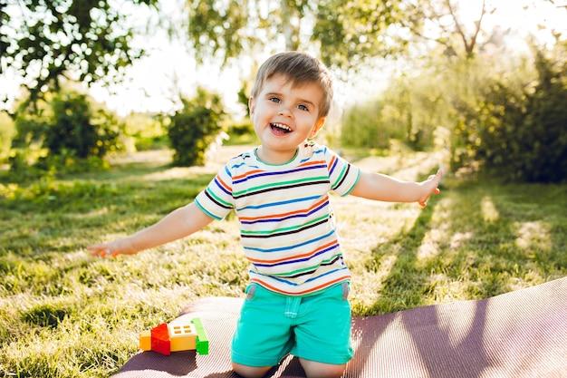 Kleine schattige jongen ziet er gelukkig uit in de zomertuin met zijn speelgoedhuis.