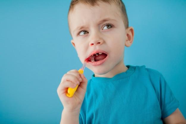 Kleine schattige jongen zijn tanden poetsen op blauwe achtergrond.